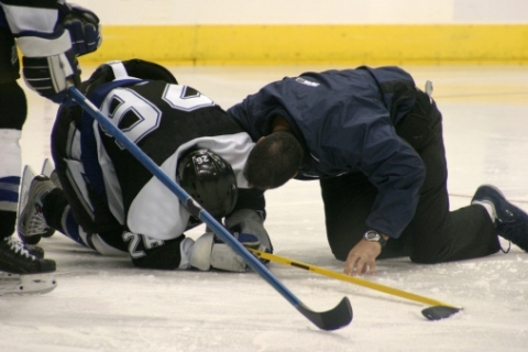 A hockey player huddles on the ice after a hard hit