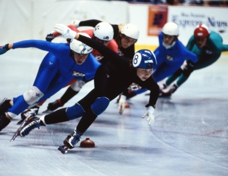 A group of speed skaters round the turn