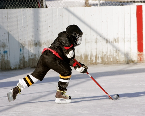 Young hockey player practices on an outdoor rink