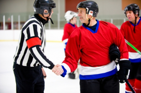 A hockey player and ref shake hands after the game