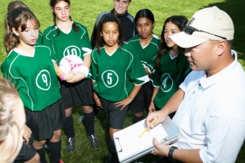 Un entraineur illustre un jeu pour son équipe