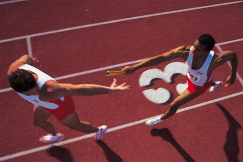 Baton is passed to another runner during a relay race