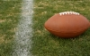 A football lays on the grass near a boundary line