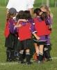 Les jeunes footballeurs se blottissent autour de l'entraîneur
